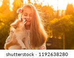 Stock photo young caucasian girl with a long blond hair holding a puppy outdoor in the autumn garden dog 1192638280