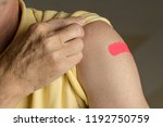 Small photo of Senior caucasian man holding up shirt sleeve to show the sticking plaster after a flu jab in shoulder