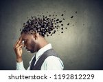 Small photo of Memory loss due to dementia or brain damage. Side profile of a sad man losing parts of head as symbol of decreased mind function.