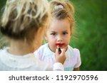 baby apply red lipstick on lips ...   Shutterstock . vector #1192970596