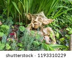 Small photo of Garden gnome with impish smile thinking - Clay dwarf in garden