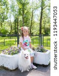 Stock photo beautiful little girl sitting on bench in park with her adorable white pomeranian dog 1193447053