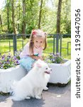 Stock photo beautiful little girl sitting on bench in park with her adorable white pomeranian dog 1193447056