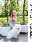 Stock photo beautiful little girl sitting on bench in park with her adorable white pomeranian dog 1193447059