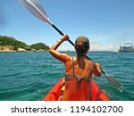 young girl paddling in a kayak... | Shutterstock . vector #1194102700