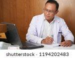 serious doctor in white coat... | Shutterstock . vector #1194202483