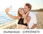 happy young couple in beachwear ... | Shutterstock . vector #1194354673