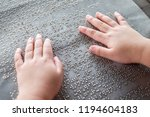 Small photo of The blind kid's hand and fingers touching the Braille letters on the metal plate to understand an information