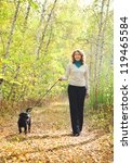 Stock photo young woman walking with black labrador retriever puppy in the autumn forest 119465584