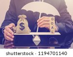 Small photo of Shareholder's wealth maximization goal and financial protection concept : Dollar bags on a simple basic balance scale with a businessman holds a white umbrella protects or guards properties or assets.
