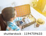woman put clothes in suitcase... | Shutterstock . vector #1194709633