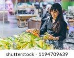 woman choosing corn in grocery... | Shutterstock . vector #1194709639