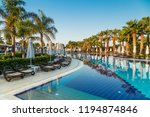 hotel pool with sun beds and... | Shutterstock . vector #1194874846