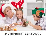 Woman with santa hat and her kids dressed as reindeer and elf decorating christmas cookies - stock photo