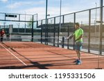 man playing padel in a orange... | Shutterstock . vector #1195331506