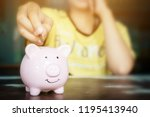 female hand putting coin in... | Shutterstock . vector #1195413940