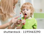 mother teaching and helping... | Shutterstock . vector #1195463290