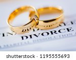 Small photo of Two broken golden wedding rings divorce decree document. Divorce and separation concept