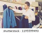 young shopaholic man chousing... | Shutterstock . vector #1195599493