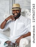 a smiling black man in a white... | Shutterstock . vector #1195637263