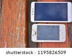 broken phone on wooden... | Shutterstock . vector #1195826509