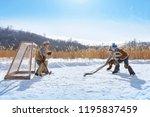 boys play hockey on a frozen... | Shutterstock . vector #1195837459
