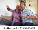 two men watching football game... | Shutterstock . vector #1195940680