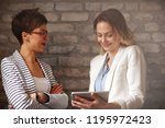 two women looking on ipad and...   Shutterstock . vector #1195972423
