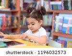little girl indoors in front of ... | Shutterstock . vector #1196032573