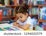 little girl indoors in front of ... | Shutterstock . vector #1196032579