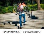 woman carrying a mountain bike... | Shutterstock . vector #1196068090