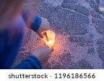 a woman lights a candle... | Shutterstock . vector #1196186566
