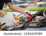 young man charging battery car... | Shutterstock . vector #1196319589