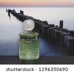 Small photo of Eau de Rochas, fragrance for ladies, big perfume bottle in front of the picture of a groyne in the sea Kassel, Germany, September 15, 2018 : Rochas is a French perfume provider from Paris.