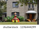 Small photo of Pretty stone house with awning and fall wreath on door and many pumpkins on porch and big blowup turkey in landscaped front yard