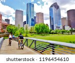 Stock photo bicyclists cross wooden bridge in buffalo bayou park with a beautiful view of downtown houston 1196454610