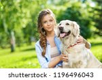 Stock photo young woman with golden retriever dog in the summer park 1196496043