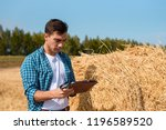 young farmer with tablet next...   Shutterstock . vector #1196589520