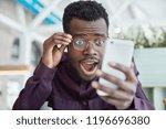 shocked dark skinned young man...   Shutterstock . vector #1196696380