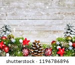 Composition of fir branches, fir cones and Christmas decor on a white wooden background. Place for text.