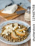 Lentil salad with caramelized pears and Roquefort cheese on a blue plate - stock photo