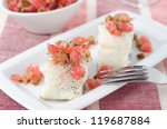 Baked cod with grapefruit salsa on white dish closeup - stock photo