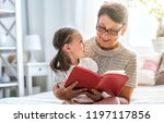 grandmother reading a book to... | Shutterstock . vector #1197117856