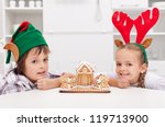 Happy christmas time - children with their gingerbread house, copyspace - stock photo