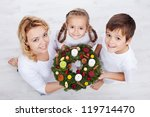 Woman with two kids holding advent wreath - holidays in the family - stock photo