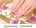 Woman hands with french manicure and flowers in bamboo bowl with water - stock photo