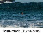 Surfer Sitting On Surfboard In...