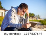 sad young man with a tablet... | Shutterstock . vector #1197837649