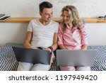young couple sitting on bed in... | Shutterstock . vector #1197949420
