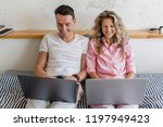 young couple sitting on bed in... | Shutterstock . vector #1197949423